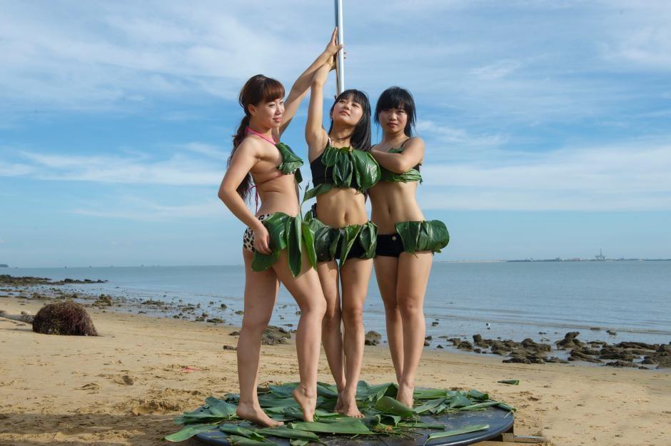 Gái trẻ mặc bikini lá dong múa cột giữa biển - 1