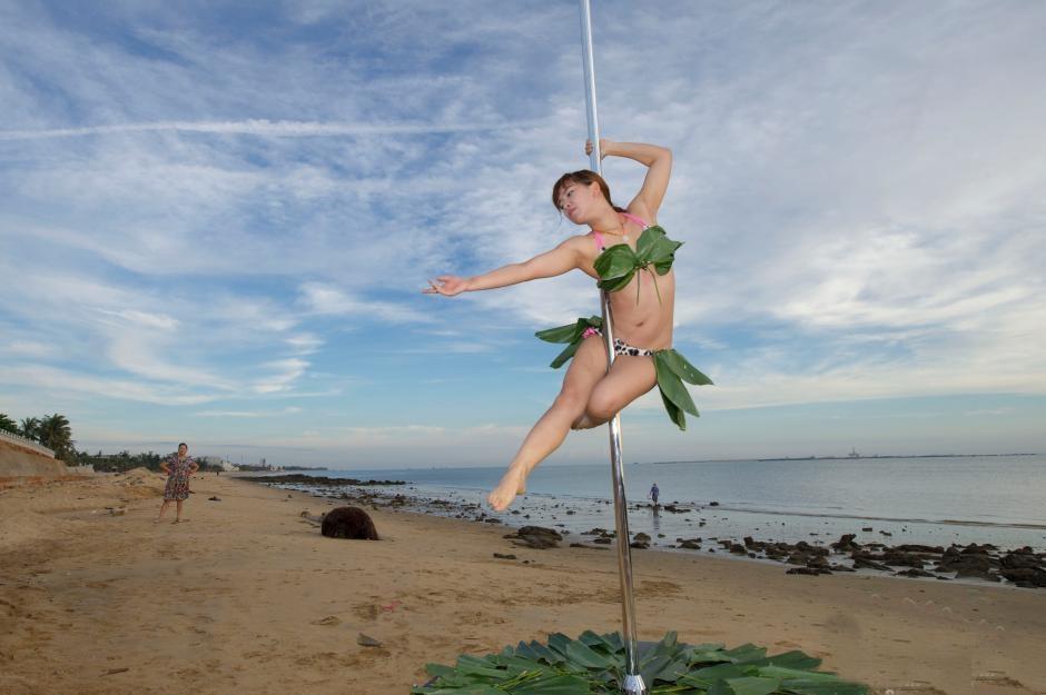 Gái trẻ mặc bikini lá dong múa cột giữa biển - 3