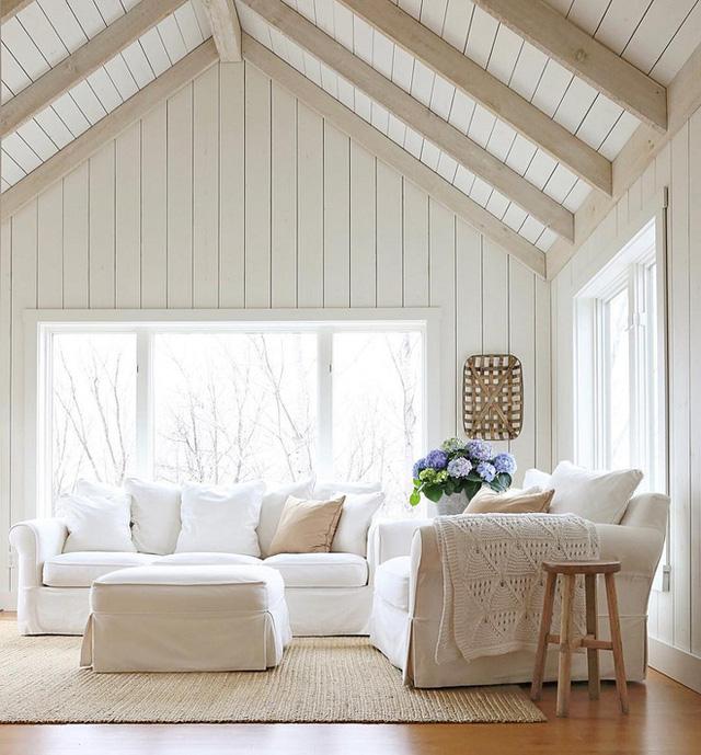 Một phòng khách có màu sắc trung hòa được làm mát hơn với ván gỗ phủ trắng trên trần nhà và đồ nội thất dệt khác.