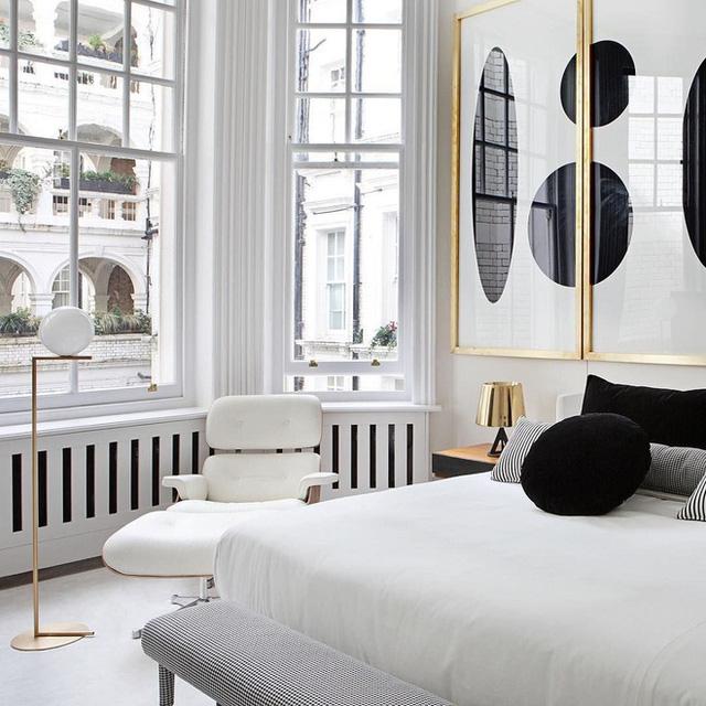 Bức tranh tường trắng đen với ý nghĩa trừu tượng trong các khung bằng vàng được thêm vào phòng ngủ màu trắng.