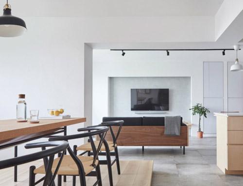 Nhà chỉ sử dụng các màu đơn giản như trắng, xám hay gỗ. Bàn ăn nằm trên một phần sàn được nâng cao tách biệt với các khu vực khác trong nhà.