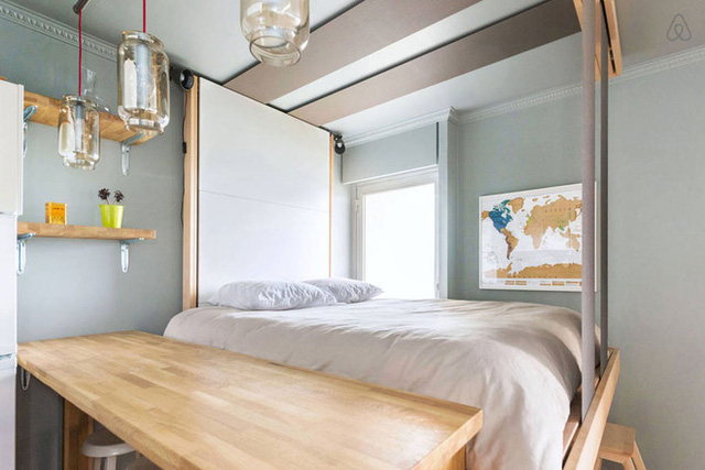 Giường ngủ được bố trí đơn giản với nệm, chăn, có khung cửa sổ ngập tràn ánh sáng tự nhiên và trang trí điểm nhấn từ bản đồ treo tường.
