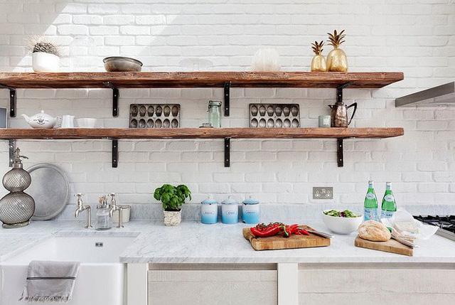 Nhà bếp toàn màu trắng từ tường với các kệ mỏng và dài đến từ gỗ.