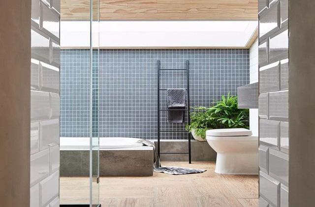 Phòng vệ sinh được thiết kế phía sau ngôi nhà. Không gian giao hòa với thiên nhiên nhờ màu xanh cây cỏ làm màu nhấn. Sự hài hòa giữa màu trắng và ghi xám tăng thêm nét hiện đại và tiện nghi, ưa nhìn cho không gian thư giãn.