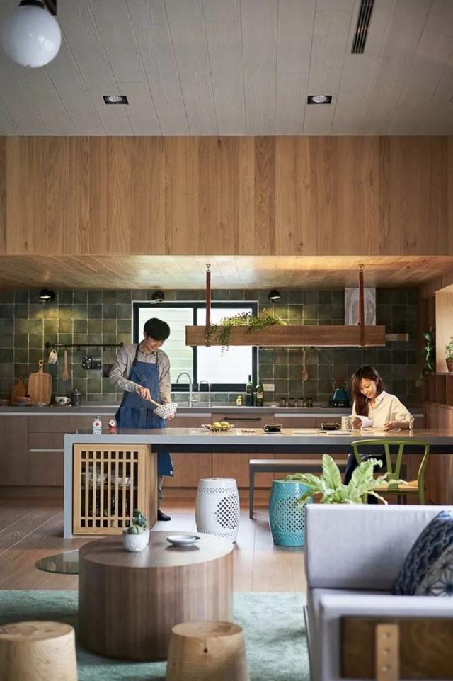 Góc bếp xinh xắn với thiết kế tủ gỗ kết nối với sàn cùng chất liệu. Phía trần được ốp gỗ giúp góc bếp nổi bật nét đẹp tiện nghi và vẻ gọn xinh. Bếp như trái tim của ngôi nhà, một chút nhấn nhá của của gạch ốp tường giúp cho góc bếp rộng hơn, bình yên và tĩnh tại hơn.