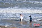 Bất chấp bão cấp 12, hàng trăm cặp đôi chụp hình cưới trên biển