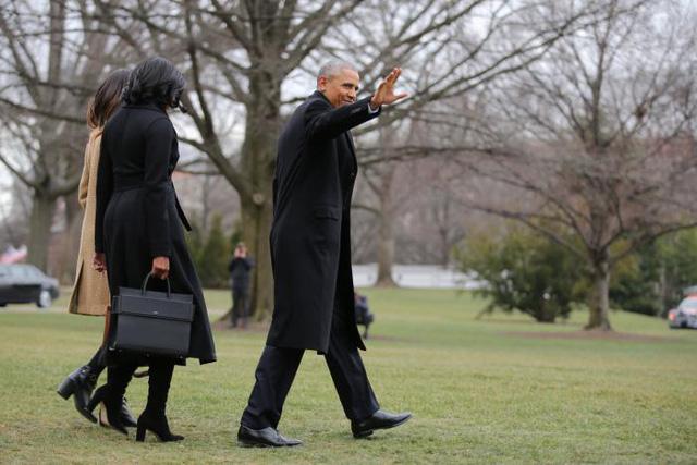 Tổng thống Obama vẫy chào khi cùng Đệ nhất phu nhân Michelle và con gái Sasha rời Nhà Trắng để lên chuyến bay về Chicago. (Ảnh: Reuters)